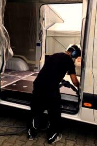 Ein KCN-Mitarbeiter baut eine Holzunterkonstruktion in den Transporter-Laderaum.